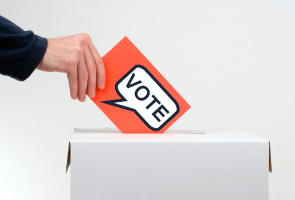 Hand putting an orange card with 'Vote' written on it into a box